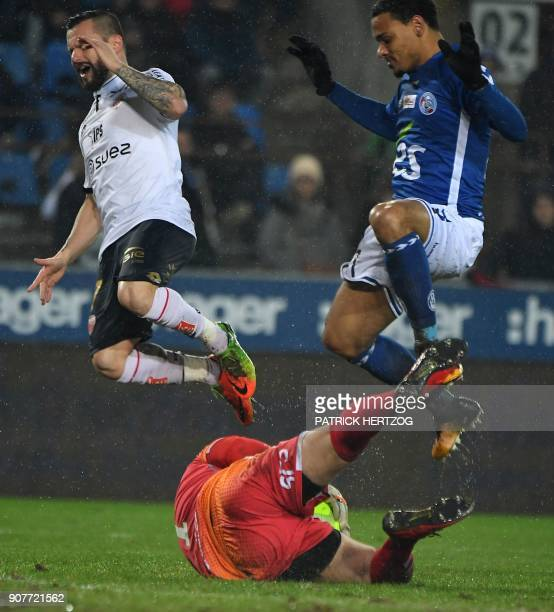 Strasbourg's French goalkeeper Landry Bonnefoi and French defender Kenny Lala vie with Dijon's French midfielder Frederic Sammaritano during the...