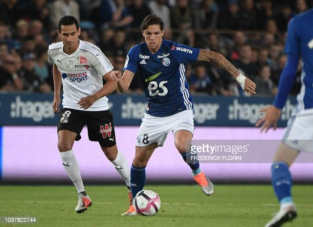 Strasbourg's French midfielder Jonas Martin vies with Amiens' Brasilian forward Paulo Ganso during the French L1 football match between Strasbourg...