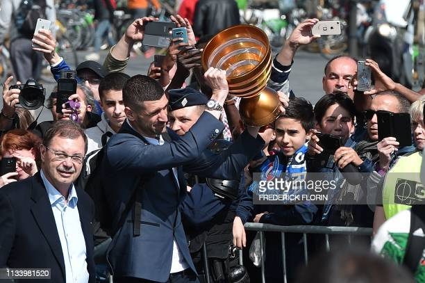 Strasbourg's Serbian defender Stefan Mitrovic holds up the Coupe de la Ligue trophy as he arrives on March 31 2019 in Strasbourg city center to...