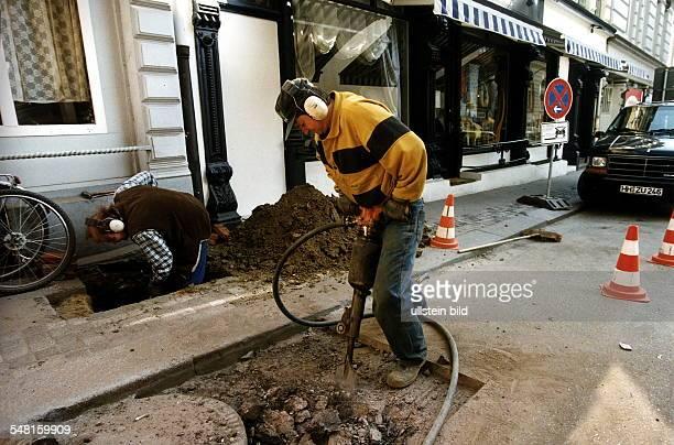 Ein Arbeiter mit einem Presslufthammer und ein Arbeiter mit Schaufel in einer Baugrube auf einem Gehweg 1998