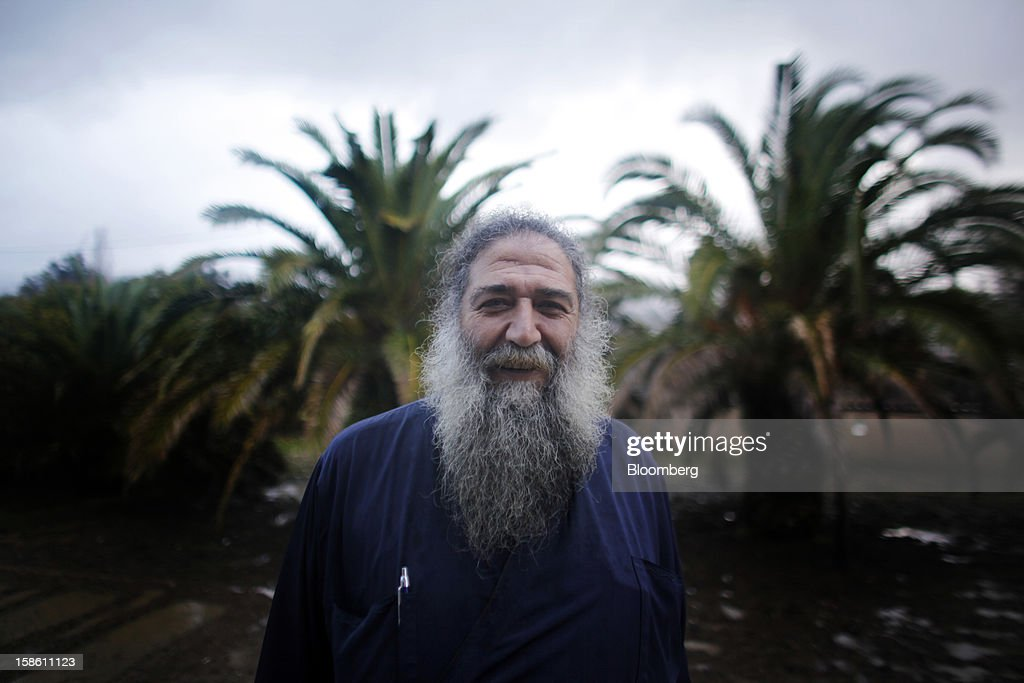 Stratis Dimou, a Greek Orthodox priest, poses for a photograph in the yard of a house he uses as a storage room in the village of Kerami on the island of Lesbos, Greece, on Sunday, Dec. 9, 2012. In recent months, Lesbos has become a hot spot for migrants as Greece struggles to cope with waves of refugees from Middle Eastern conflict even as it reels from economic crisis at home. Photographer: Kostas Tsironis/Bloomberg via Getty Images