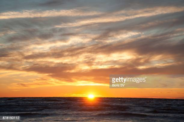 Stratocumulus Clouds during orange sunset over the sea