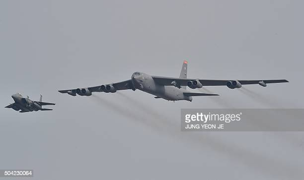 Stratofortress is escorted by a South Korean F15K fighter jet as it flies over the Osan Air Base in Pyeongtaek south of Seoul on January 10 2016 The...