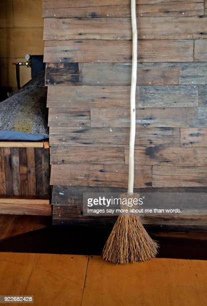 Straw broom against a wooden wall.