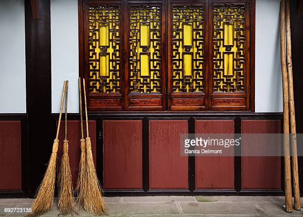 Straw brooms leaning on wall of Baoguang Temple, Chengdu, Sichuan, China