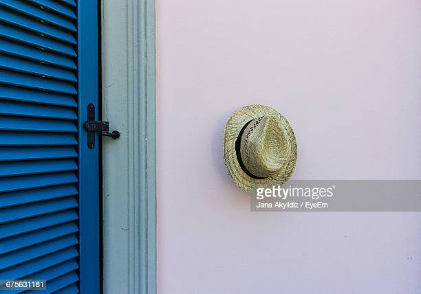 Straw Hat Hanging On Wall By Door At Home