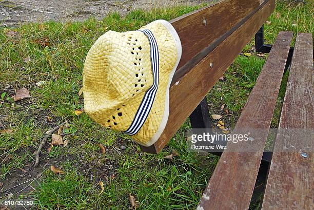 Straw hat, left behind on a wooden park bench.