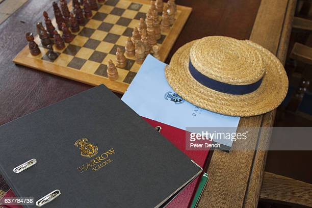 A straw hat on a pupils study desk in the library at Harrow School Harrow School is an English independent school for boys situated in the town of...