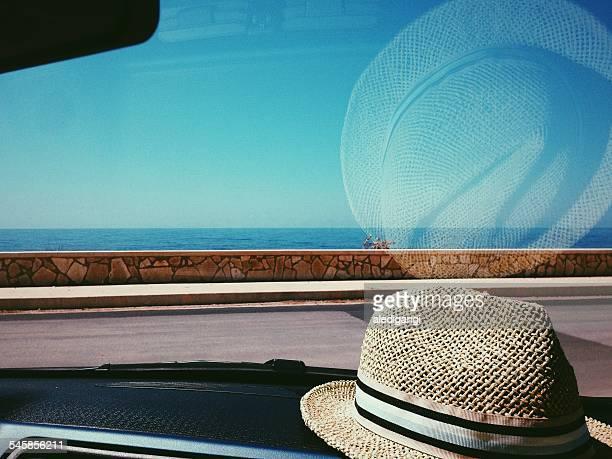 Straw hat on dashboard of car
