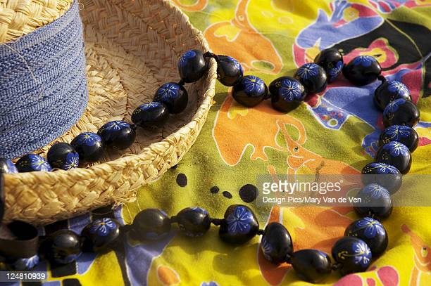 Straw hat with blue band on Colorful pareo (sarong) with hand painted kukui nut lei.