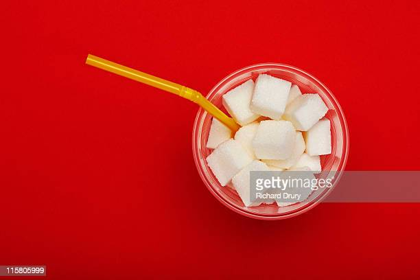Straw in plastic glass filled with sugar cubes