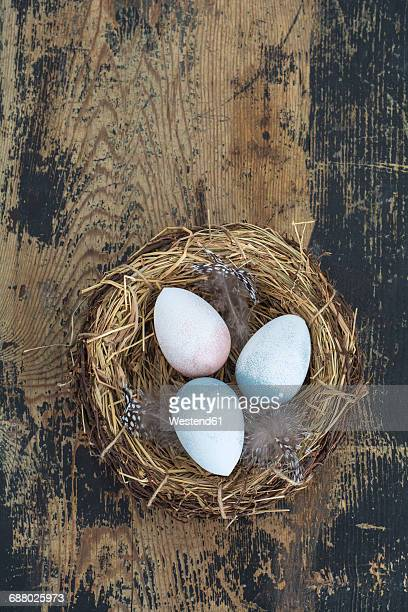 Straw nest with Easter eggs on wood