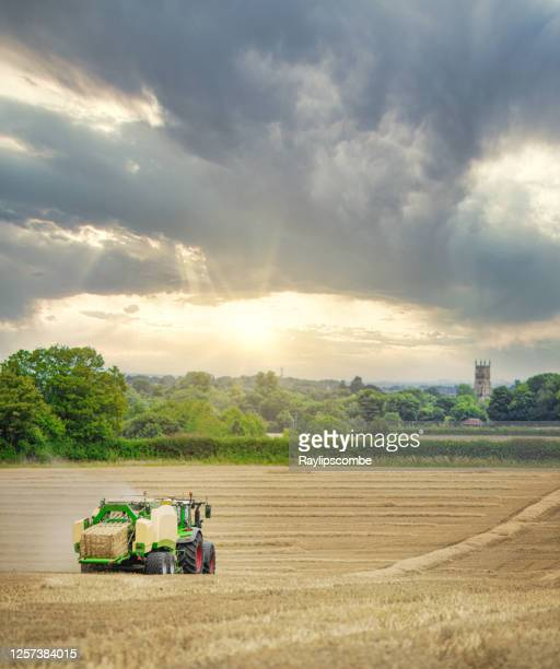 straw or hay baler machine pulled by a tractor, discharging a compacted straw bale from the rear in a field of recently harvested barley on the outskirts of cirencester in the cotswolds - cirencester stock pictures, royalty-free photos & images