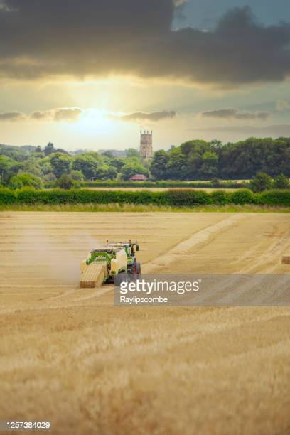 straw or hay baler machine pulled by a tractor, discharging a compacted straw bale from the rear in a field of recently harvested barley on the outskirts of cirencester in the cotswolds - landscape stock pictures, royalty-free photos & images