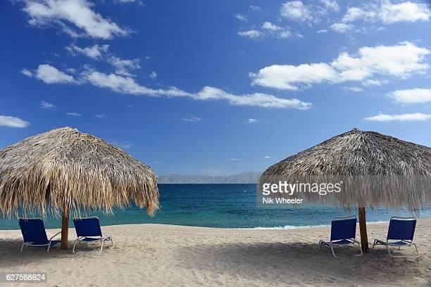 straw palapas on sandy beach on Sea of Cortez near La Paz, Baja California Peninsula, Mexico
