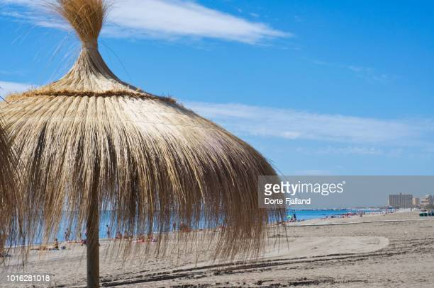 A straw parasol on a sunny beach with a blue sky and some people sunbathing