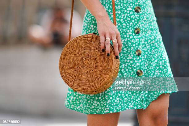 Straw round bag, and a green flower print dress are seen, on May 26, 2018 in Paris, France.