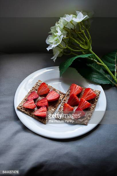 Strawberries and almond butter on a crisp bread