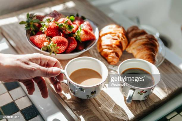 Strawberries, croissants and coffee in kitchen