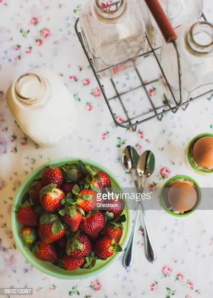 Strawberries, eggs and milk on table