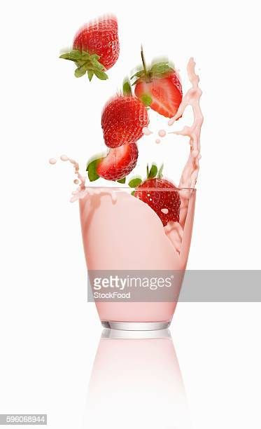 Strawberries falling into a glass of strawberry milk