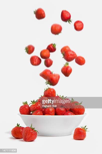 Strawberries falling into a white bowl