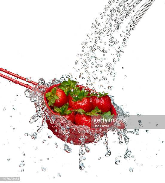strawberries in a red colander - colander stock photos and pictures