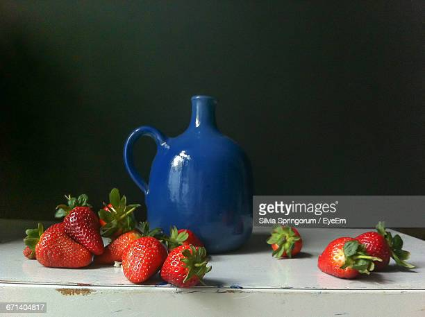 Strawberries In Front Of Vase On Table