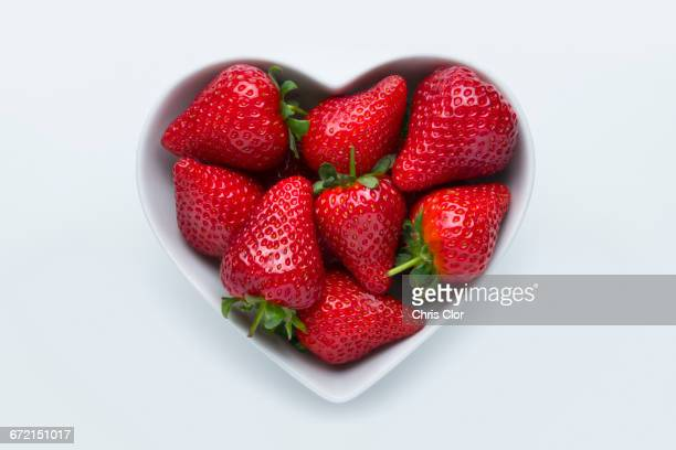Strawberries in heart-shape bowl on white background