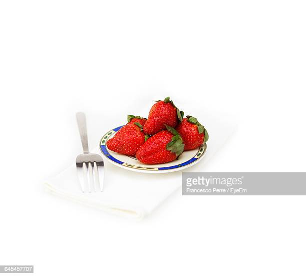 Strawberries In Plate By Fork On White Background