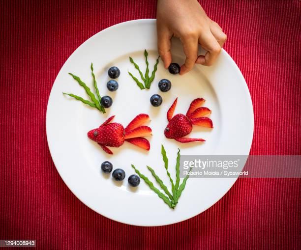 strawberries in shape of fish food creation, flat lay - representar fotografías e imágenes de stock