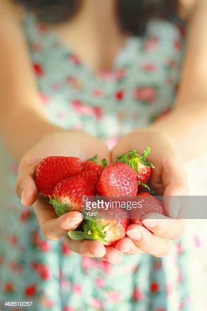 Strawberries on hands.