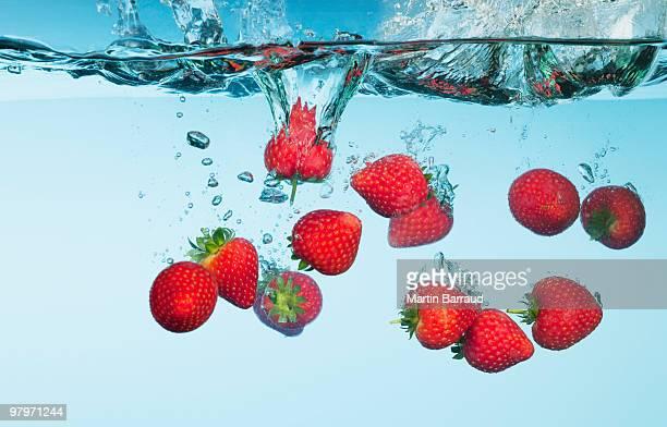 Strawberries splashing in water