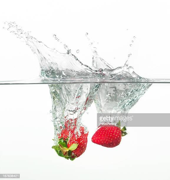 2 strawberries splashing into the water