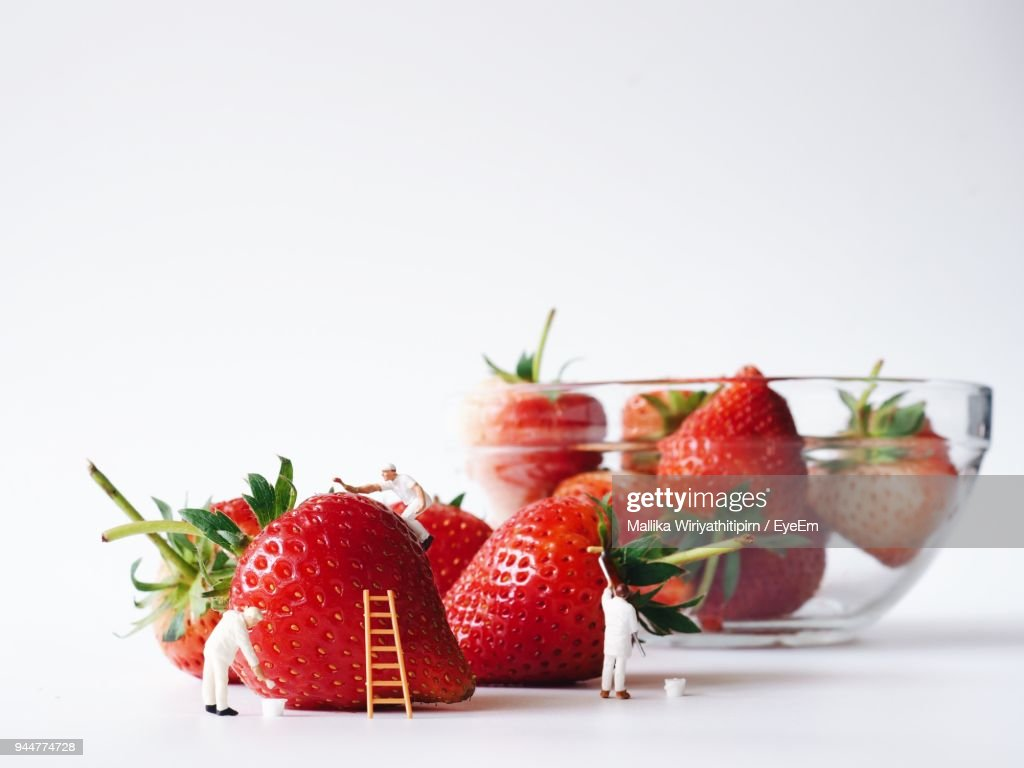 Strawberries With Figurines And Bowl Against White Background : Stock Photo