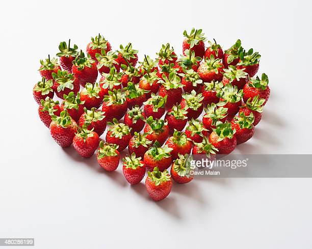 Strawberries with stems arranged in a heart shape