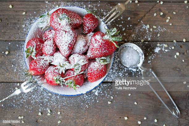 Strawberries with sugar on the wood table