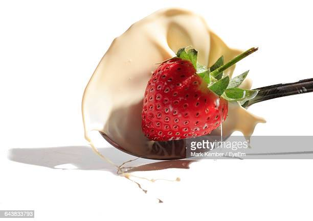 Strawberry And Cream Splashing In Spoon Over White Background
