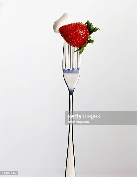 Strawberry and whipped cream on fork