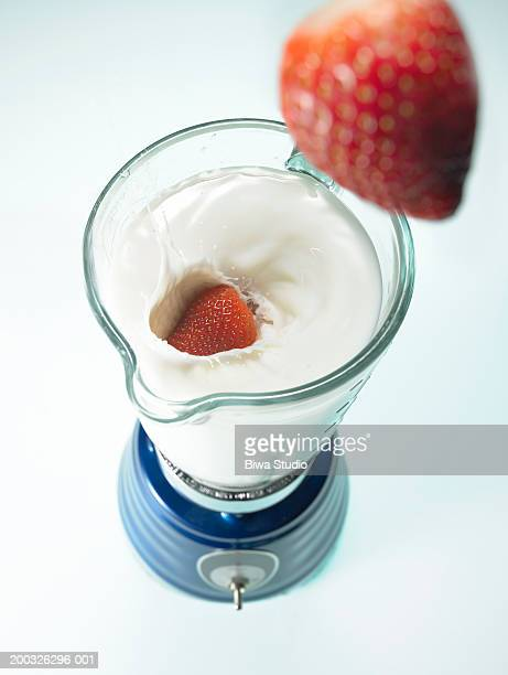 Strawberry and yogurt in blender, strwberry above, elevated view