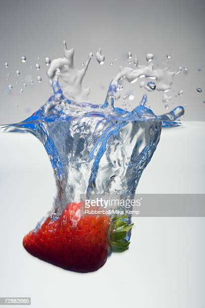 Strawberry being dropped into water