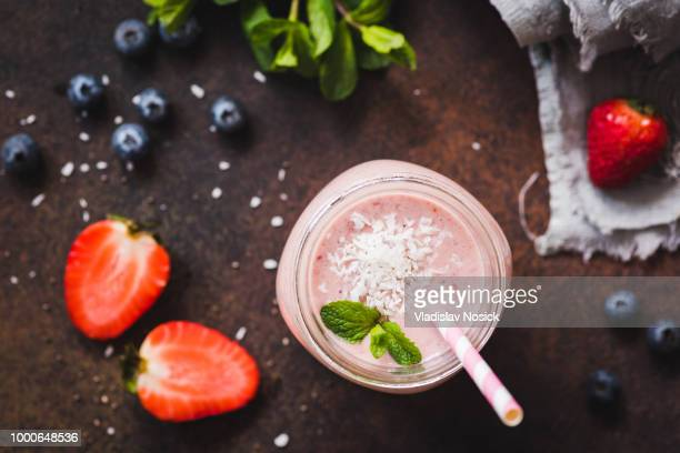Strawberry coconut smoothie in jar with pink drinking straw, top view, selective focus