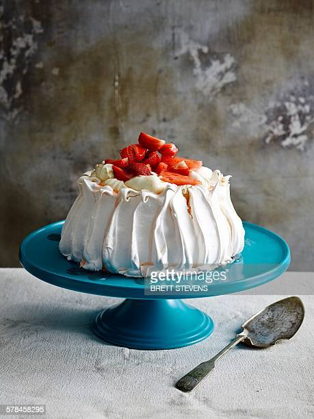 Strawberry covered pavlova on blue ceramic cake stand with cake server