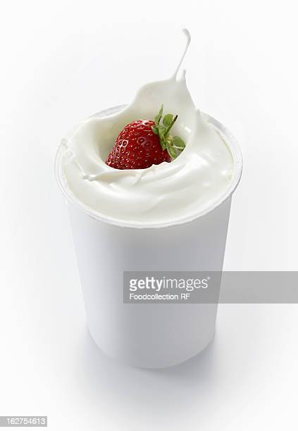 Strawberry falling into cup of yoghurt