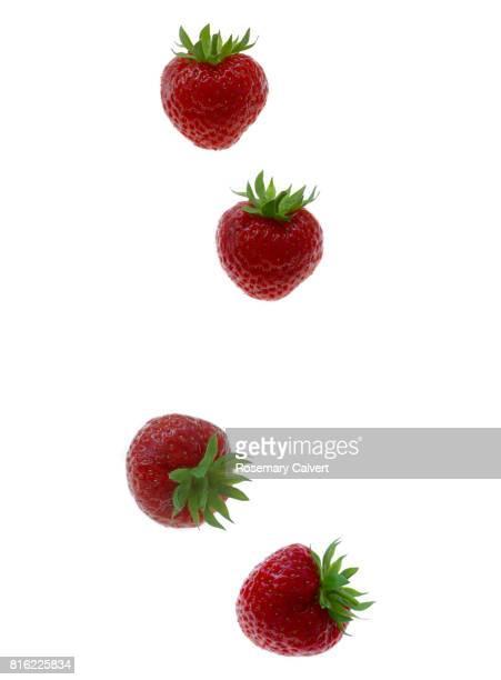 Strawberry four times as it falls on white.