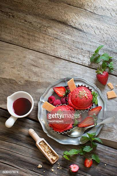 Strawberry ice cream balls with fresh berries and mint leaf served with strawberry syrup on moody rustic wooden table top.