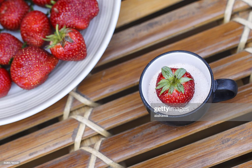 Strawberry in a cup of milk on bamboo table : Stock Photo