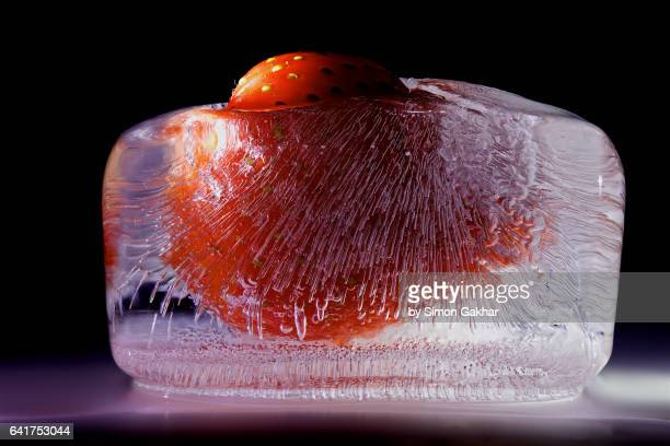 strawberry in ice - durability stock photos and pictures