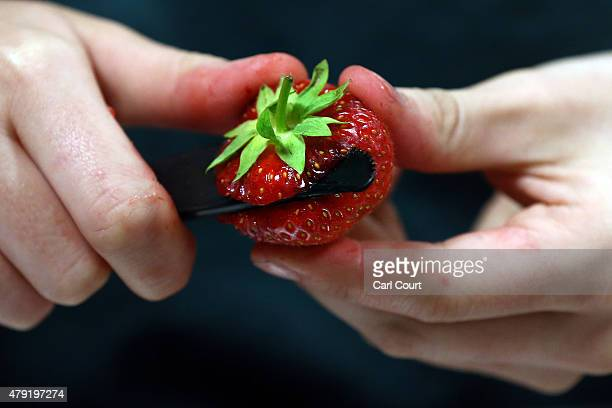 A strawberry is prepared on day four of the Wimbledon Lawn Tennis Championships at the All England Lawn Tennis and Croquet Club on July 2 2015 in...