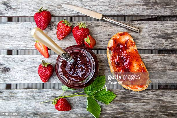 Strawberry jam in glass, strawberries and bread with jam on wood